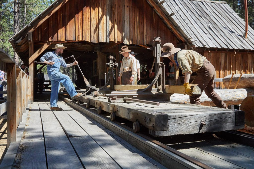 sawmill being operated by three men in turn-of-the-century clothing