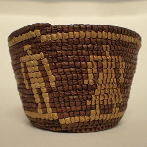 small brown woven basket with lighter colored bands around the top and bottom and two stick figures, one representing a man and one representing a woman