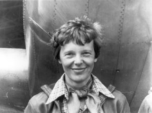 black and white photo of Amelia Earhart standing under the nose of her Lockheed Model 10 plane, it's a close-up shot with her smiling, wearing large collared shirt and scarf tied around the neck